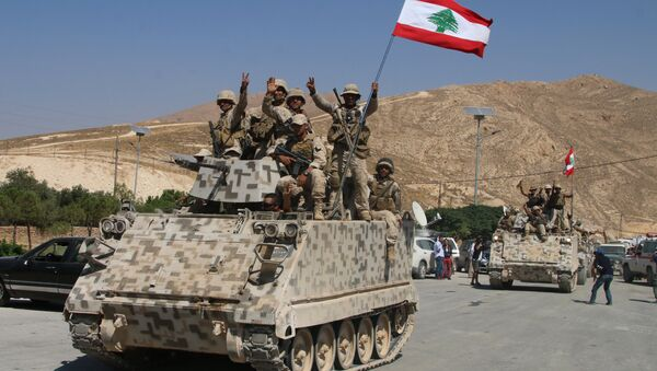 Lebanese army soldiers sit a top an armoured personnel carrier (APC) as they drive in the eastern town of Ras Baalbek, on August 21, 2017, upon returning from the mountainous frontline where an offensive against the Islamic State group on the country's eastern border with Syria after capturing a third of the territory IS held in the region. - Sputnik International