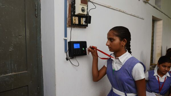 An Indian schoolgirl uses an electronic ID card to mark her attendance at a school in the first Indian 'Digital Village' in Akodara, some 90 kms from Ahmedabad, on 8 July 2015. - Sputnik International