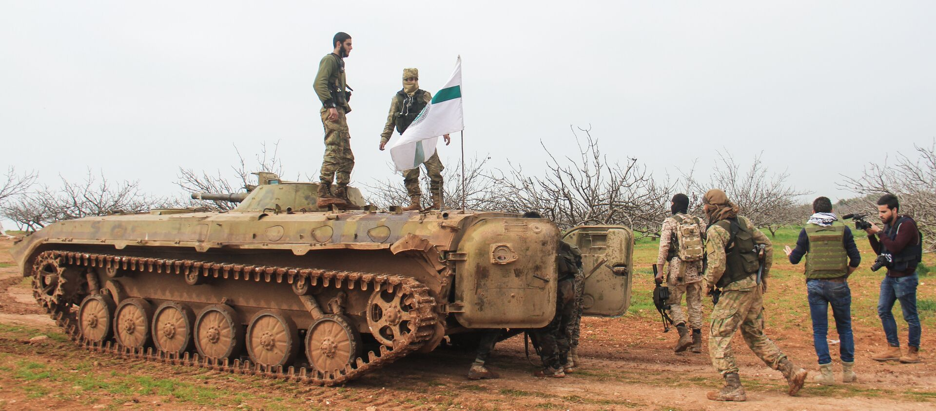 A picture taken on March 22, 2017 near the town of Maardes in the countryside of the central Syrian province of Hama, shows rebel fighters walking past an armoured vehicle carrying the flag of the Tahrir al-Sham rebel alliance - Sputnik International, 1920, 04.04.2021