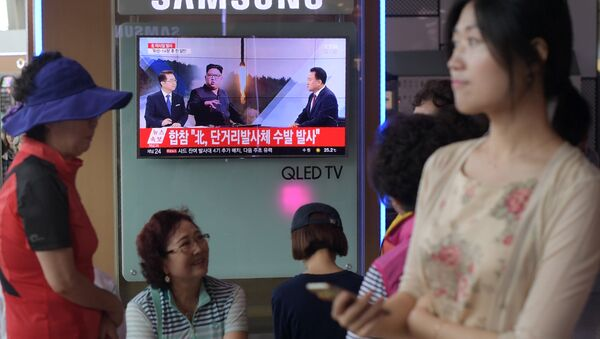 People are seen past a television screen showing a file image of North Korean leader Kim Jong-Un (C) as news anchors (on screen, L and R) provide coverage of this morning's North Korean missile launch, at a railway station in Seoul on August 26, 2017 - Sputnik International