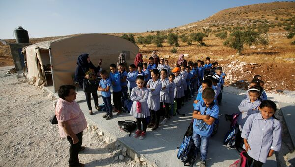 Palestinian schoolchildren queue outside a tent where they attend lessons after Israeli troops confiscated caravans used as school classrooms, due to the lack of an Israeli-issued construction permit, in the West Bank village of Jubbet Al Dhib, near Bethlehem August 24, 2017 - Sputnik International