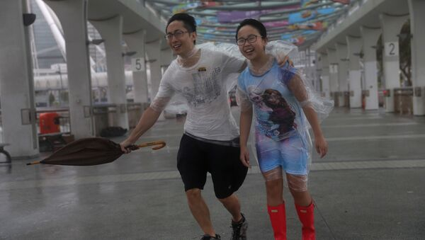 People play in the strong wind from Typhoon Hato on the waterfront of Victoria Habour in Hong Kong, Wednesday, Aug. 23, 2017. - Sputnik International
