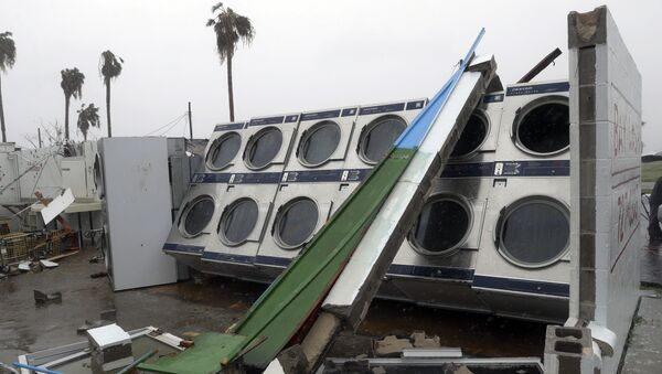 Clothes dryers are exposed to the elements after a laundromat lost its roof and portions of walls in the wake of Hurricane Harvey. - Sputnik International