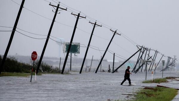 A man walks through floods waters and onto the main road after surveying his property which was hit by Hurricane Harvey in Rockport, Texas, U.S. August 26, 2017. - Sputnik International