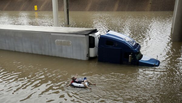A man floats past a truck submerged on a freeway flooded by Tropical Storm Harvey on Sunday, Aug. 27, 2017, near downtown Houston. - Sputnik International