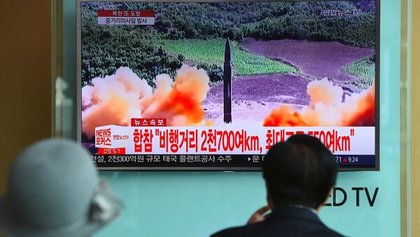 People watch a television news screen showing file footage of a North Korean missile launch, at a railway station in Seoul on August 29, 2017. - Sputnik International
