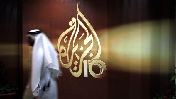 A Qatari employee of Al Jazeera Arabic language TV news channel passes by the logo of Al Jazeera in Doha, Qatar. (File) - Sputnik International