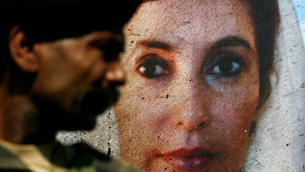A portrait of Benazir Bhutto on the side of her open-air vehicle is splattered with bomb residue, as it is guarded by a Pakistani soldier in Karachi, Pakistan, on Friday Oct. 19, 2007, following an assassination attempt on Thursday. - Sputnik International
