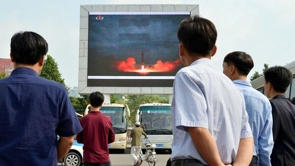 North Koreans watch a news report showing North Korea's Hwasong-12 intermediate-range ballistic missile launch on electronic screen at Pyongyang station in Pyongyang, North Korea, in this photo taken by Kyodo August 30, 2017 - Sputnik International
