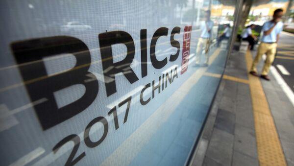 A man stands near a billboard advertising the 2017 BRICS Summit at a bus shelter in Xiamen in southeastern China's Fujian Province, Saturday, Sept. 2, 2017 - Sputnik International