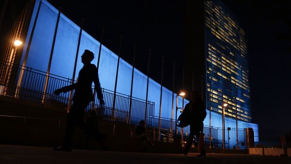 Pedestrians walk by United Nations Headquarters, lit up in blue light, a day in advance of the 70th Anniversary of the U.N., in New York City. File Photo. - Sputnik International