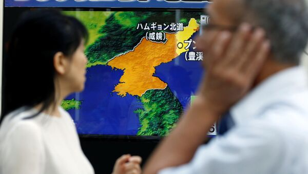 People walk past a street monitor showing a news report about North Korea's nuclear test, in Tokyo, Japan, September 3, 2017 - Sputnik International