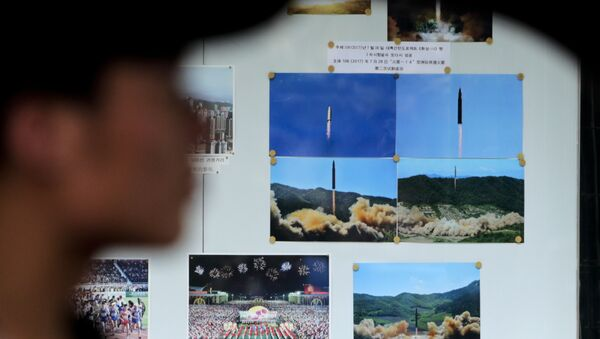 A man drives his car past a display board showing photos of ballistic missile launches in North Korea outside the North Korean Embassy in Beijing - Sputnik International