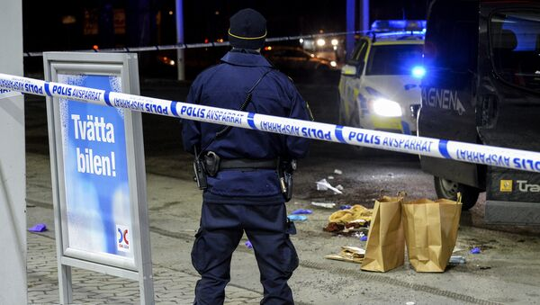 A police officer stands inside a roped off an area on a gas station in Fittja, Sweden, where a man was found severely injured in a minivan after being shot at when taking part in a pro-Kurdish demonstration Saturday, Feb. 13, 2016 - Sputnik International