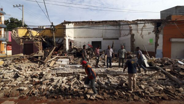 Residents stand on debris of a partially collapsed building felled by a massive earthquake in Juchitan, Oaxaca state, Mexico, Friday, Sept. 8, 2017. - Sputnik International