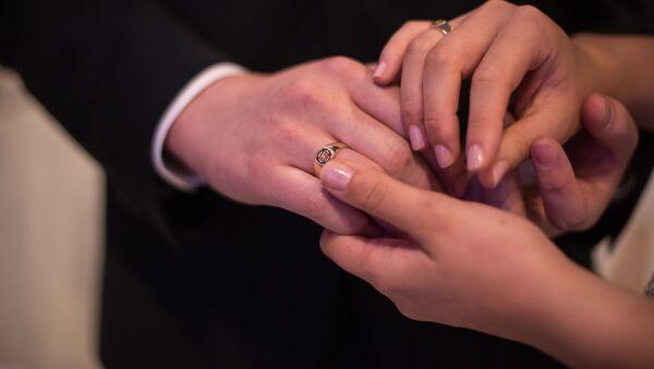 Руки жениха и невесты, участвующих в массовой свадьбе в Южной Корее - Sputnik International