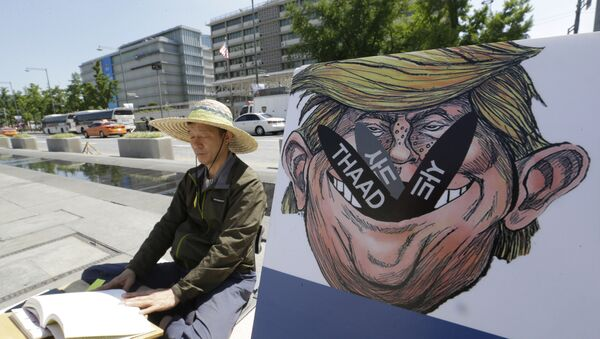 A South Korean protester sits next to a poster with an illustration of U.S. President Donald Trump to oppose a plan to deploy an advanced U.S. missile defense system called Terminal High-Altitude Area Defense, or THAAD, near the U.S. Embassy in Seoul Monday, June 5, 2017 - Sputnik International