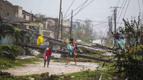 Residents walk near downed power lines felled by Hurricane Irma, in Caibarien, Cuba, Saturday, Sept. 9, 2017 - Sputnik International