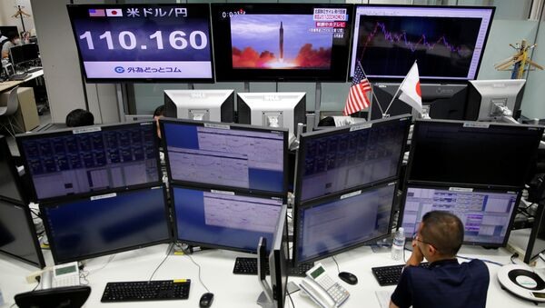 An employee of a foreign exchange trading company works in front of monitors showing TV news on North Korea's missile launch (top C) and the Japanese yen's exchange rate against the U.S. dollar (top L) in Tokyo, Japan, September 15, 2017 - Sputnik International