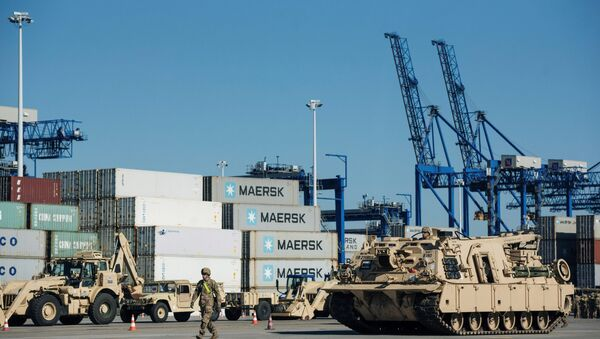 Soldiers walk near U.S. military equipment which arrived as part of NATO mission at port in Gdansk, Poland - Sputnik International