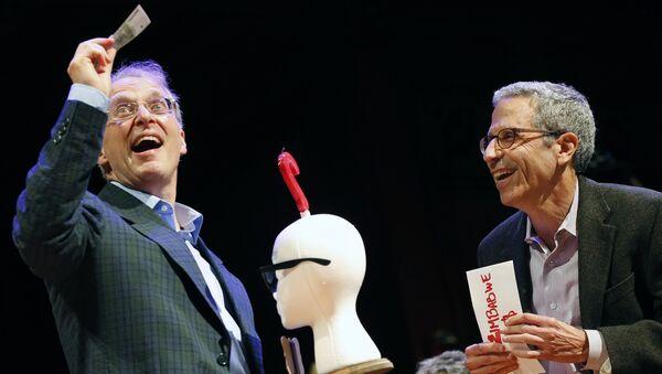 James Heathcote, left, reacts after receiving the Ig Nobel Anatomy Prize from Nobel laureate Eric Maskin (economics, 2007) during ceremonies at Harvard University in Cambridge, Mass - Sputnik International