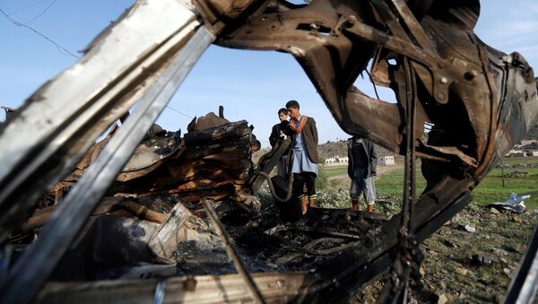 People look at the wreckage of a taxi car destroyed by a Saudi-led air strike on a checkpoint of the armed Houthi movement near Sanaa, Yemen August 30, 2017 - Sputnik International