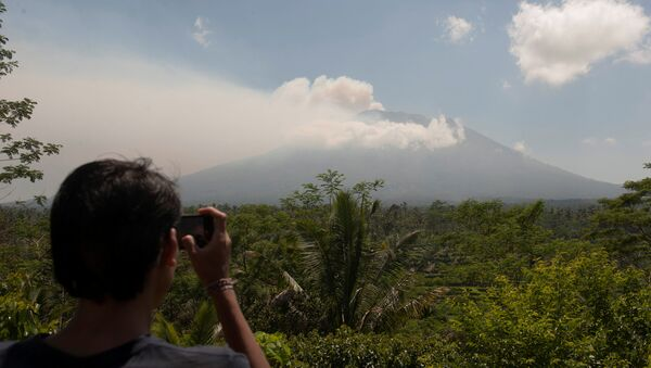 A local resident takes a picture of Mount Agung, an active volcano that authorities say is showing increased activity, from a monitoring station in Rendang Village, Karangasem on the resort island of Bali, Indonesia September 19, 2017 - Sputnik International