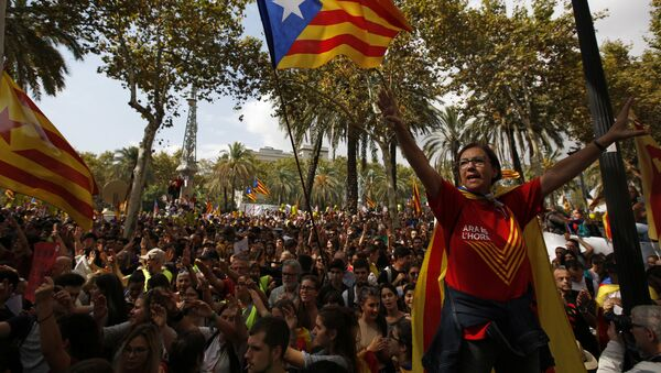 A woman gestures as others wave the estelada or Catalonia independence flags during a protest in Barcelona, Spain Thursday, Sept. 21, 2017. - Sputnik International