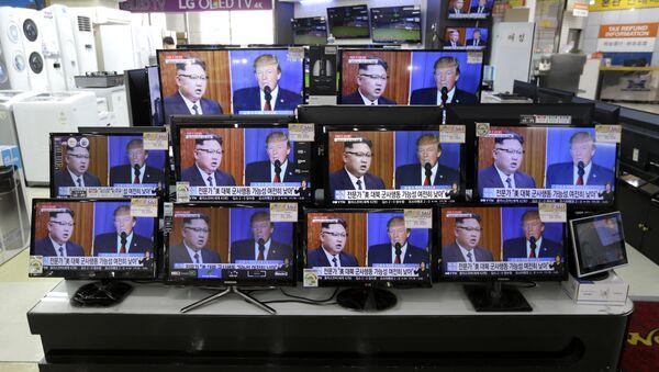 TV screens show a news program with an image of U.S. President Donald Trump and North Korean leader Kim Jong Un - Sputnik International