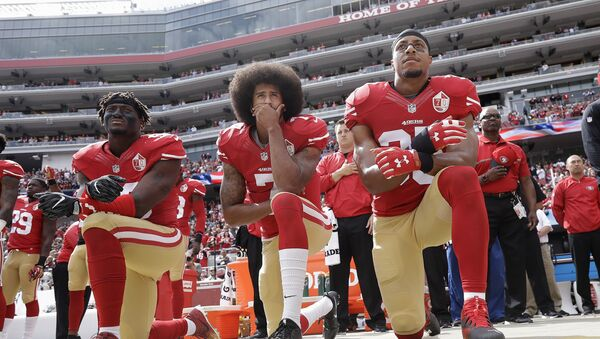 from left, San Francisco 49ers outside linebacker Eli Harold, quarterback Colin Kaepernick and safety Eric Reid kneel during the national anthem before an NFL football game against the Dallas Cowboys in Santa Clara, Calif. Since Kaepernick announced he would not stand for the song in protest of racial discrimination against blacks in the United States, many performers are now rethinking offers to sing the national anthem. - Sputnik International