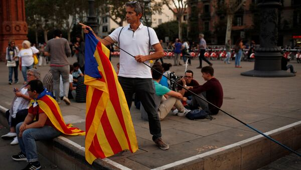 A man places an Estelada (Catalan separatist flag) on a stick during a protest outside the High Court of Justice of Catalonia in Barcelona, Spain, September 21, 2017 - Sputnik International