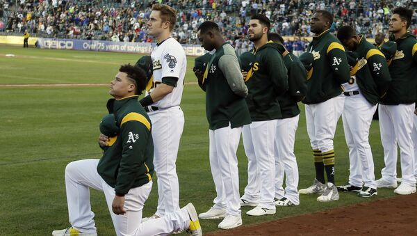 Oakland Athletics catcher Bruce Maxwell kneels during the national anthem before the start of a baseball game against the Texas Rangers Saturday, Sept. 23, 2017, in Oakland, Calif. Bruce Maxwell of the Oakland Athletics has become the first major league baseball player to kneel during the national anthem. - Sputnik International