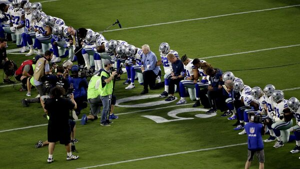 The Dallas Cowboys, led by owner Jerry Jones, center, take a knee prior to the national anthem prior to an NFL football game against the Arizona Cardinals, Monday, Sept. 25, 2017, in Glendale, Ariz. - Sputnik International