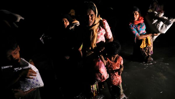 Women and children wade through the water as hundreds of Rohingya refugees arrive under the cover of darkness by wooden boats from Myanmar to the shore of Shah Porir Dwip, in Teknaf, near Cox's Bazar in Bangladesh, September 27, 2017 - Sputnik International