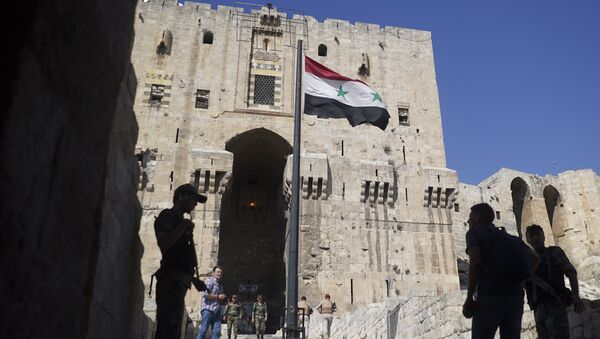 People walk into the Citadel, Aleppo's famed fortress where much of the fierce fighting took place in 2016, in Syria, Tuesday, Sept. 12, 2017 - Sputnik International