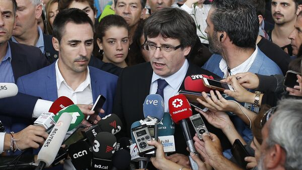 Catalan President Carles Puigdemont, centre, speaks to the media at a sports center, assigned to be a polling station by the Catalan government and where Puigdemont was originally expected to vote, in Sant Julia de Ramis, near Girona, Spain, Sunday, Oct. 1, 2017. Scuffles earlier erupted as voters protested as dozens of anti-rioting police broke into a polling station. - Sputnik International