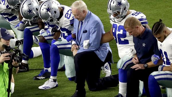In this Monday, Sept. 25, 2017, file photo, the Dallas Cowboys, led by owner Jerry Jones, center, take a knee prior to the national anthem before an NFL football game against the Arizona Cardinals in Glendale, Ariz. What began more than a year ago with a lone NFL quarterback protesting police brutality against minorities by kneeling silently during the national anthem before games has grown into a roar with hundreds of players sitting, kneeling, locking arms or remaining in locker rooms, their reasons for demonstrating as varied as their methods. - Sputnik International