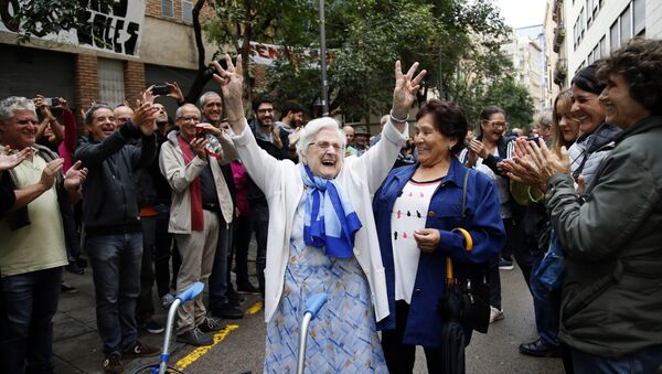 An elderly lady is applauded as she celebrates after voting at a school assigned to be a polling station by the Catalan government at the Gracia neighborhood in Barcelona, Spain, Sunday, 1 Oct. 2017. The Spanish government and its security forces are trying to prevent voting in the independence referendum, which is backed by Catalan regional authorities. Spanish officials had said force wouldn't be used, but that voting wouldn't be allowed. - Sputnik International
