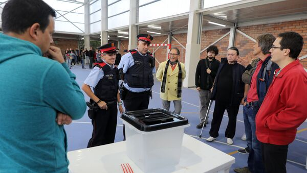 A couple of Mossos D'Esquadra (Catalan police) enter a polling station in Figueras, on October 1, 2017, on the day of a referendum on independence for Catalonia banned by Madrid - Sputnik International