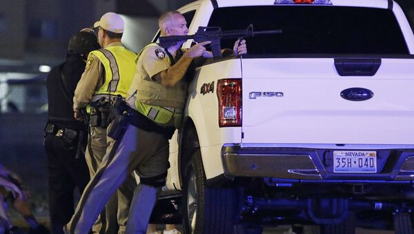 A police officer takes cover behind a truck at the scene of a shooting near the Mandalay Bay resort and casino on the Las Vegas Strip, Sunday, Oct. 1, 2017, in Las Vegas - Sputnik International