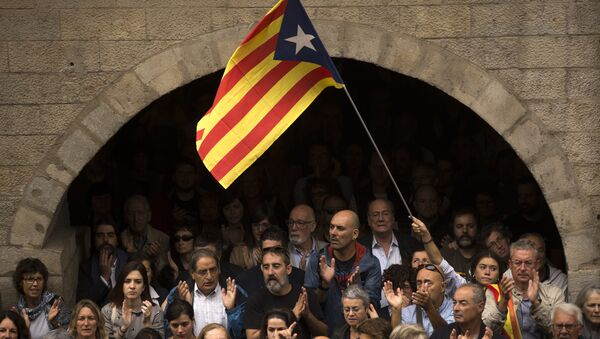 Catalan independence supporters, one waving an estelada, or Catalonia independence flag, applaud during a rally outside the city hall of Girona, Spain - Sputnik International