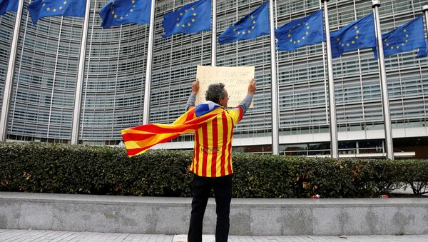 Catalan Raimon Castellvi, wearing a flag with an Estelada (Catalan separatist flag), holds a sign as he protests outside the European Commission in Brussels after Sunday's independence referendum in Catalonia, Belgium October 2, 2017 - Sputnik International