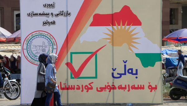 Iraqi women walk on the street, near banners supporting the referendum for independence for Kurdistan in Erbil, Iraq September 21, 2017 - Sputnik International
