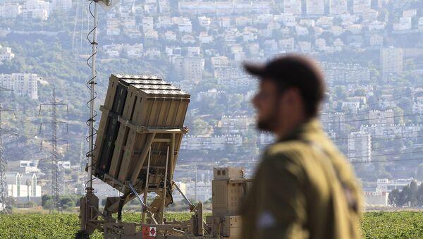 An Israeli soldier is seen next to an Iron Dome rocket interceptor battery deployed near the northern Israeli city of Haifa, Wednesday, Aug. 28, 2013.  - Sputnik International