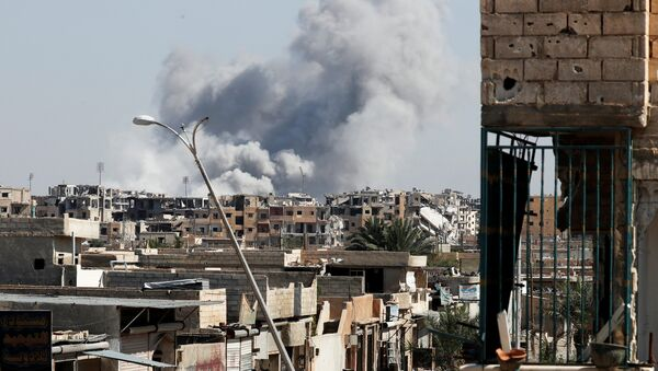 Smoke rises near the stadium where the Islamic State militants are holed up after an air strike by coalition forces at the frontline, in Raqqa, Syria October 12, 2017 - Sputnik International