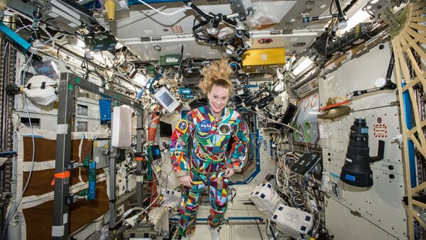 This undated handout photo from NASA shows astronaut Kate Rubins aboard the International Space Station wearing a hand-painted spacesuit decorated by childhood cancer patients at the University of Texas MD Anderson Cancer Center in Houston. NASA said Rubins will chat from the space station with patients during a 20-minute call on Friday, Sept. 16, 2016 - Sputnik International