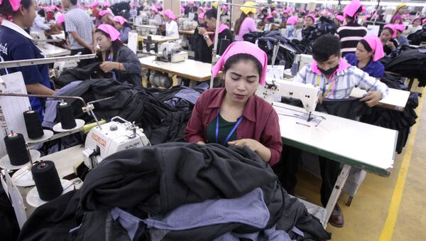 Cambodian garment workers sew clothes in a factory as they wait for visit by their Prime Minister Hun Sen at Phnom Penh Special Economic Zone in the outskirts of Phnom Penh, Cambodia, Wednesday, Aug. 23, 2017. Hun Sen on Wednesday began his plan to visit workers at factories in Cambodia. - Sputnik International