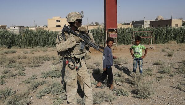 A U.S. soldier stands near Syrian children on a road that links to Raqqa, Syria, Wednesday, July 26, 2017 - Sputnik International