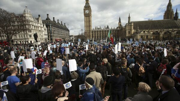 People gather in Parliament Square as part of a national day of action in support of migrants in the UK, in London with the Houses of Parliament back right, Monday Feb. 20, 2017. British lawmakers are set to hold a debate on Monday in London to consider a call for U.S. President Donald Trump to be denied an official state visit to the U.K., but the Conservative government insists the invitation remains firmly in place. - Sputnik International