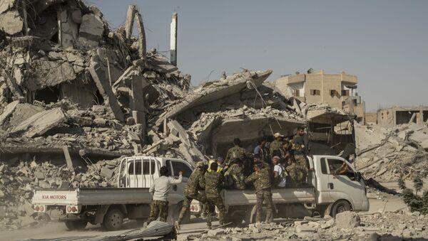 Members of the U.S.-backed Syrian Democratic Forces (SDF) ride near near the main traffic circle in Raqqa Syria, Friday, Oct. 20, 2017 - Sputnik International